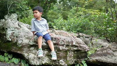 The boy sitting on a rock at the nature