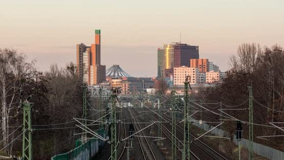 Sunset time lapse of Berlin city skyline with train traffic in foreground