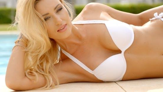 Thumbnail for Blond Frau in Bikini liegend auf Seite neben Pool