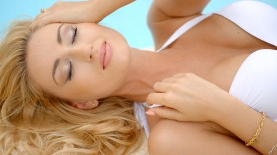 Thumbnail for Frau trägt weiße Bikini liegend mit Augen geschlossen
