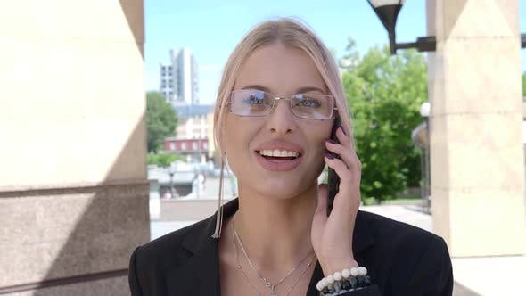 Cover Image for A Woman in a Business Suit Smiles While Talking on the Phone.