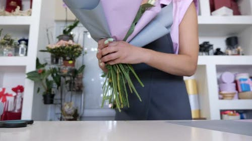 Florist is Packaging Bouquet From Roses and Leaves in Paper Closeup Hands