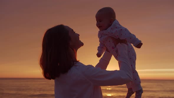 Mom hugs baby on a sunset background