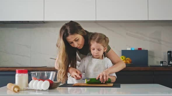 Mother and Little Daughter Hold Together Large Knife