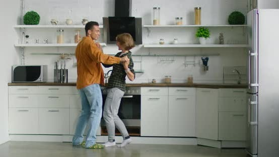 Happy Hispanic Man and Caucasian Woman Are Dancing in the Morning in Kitchen