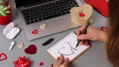 Young woman writing a card I LOVE YOU while wrapping valentine's day gift