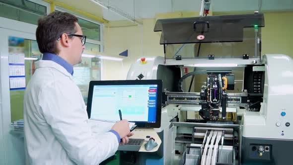 The Engineer in a White Robe and Glasses Works for the Surface Mount Technology Machine. PCB