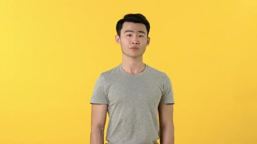 Young Asian man shrugging shoulders and rolling eyes with uncaring facial expression