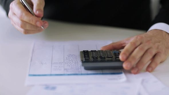 Thumbnail for Hands Counting On Calculator And Filling Papers