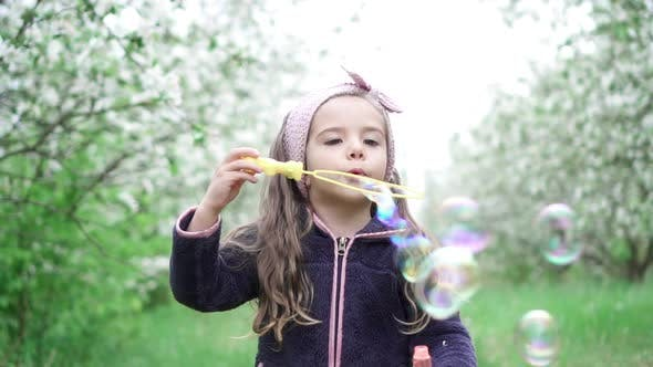 Little Girl Playing with Soap Bubbles in Blooming Garden, Slow Motion
