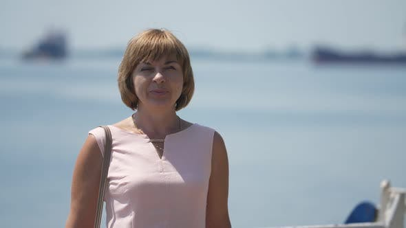 Thumbnail for Happy Blonde Woman Standing and Smiling at Dnipro River in Summer in Slo-mo