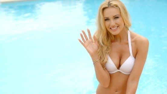 Thumbnail for blond frau in bikini neben pool winken