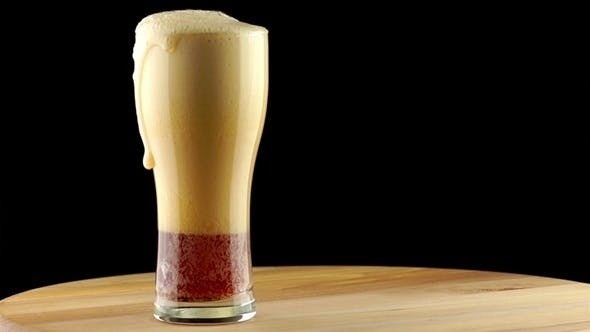 Dark Beer is Poured into a Tall Glass