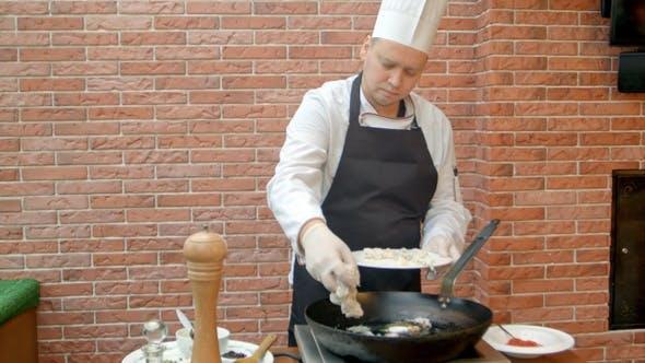 Chef putting fresh seafood to a pan