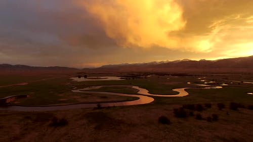 Flying over river at golden sunrise