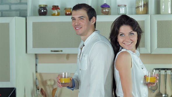 Cover Image for Couple Standing Back To Back Holding Orange Juice