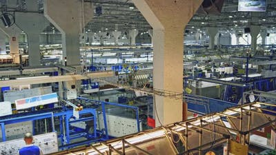View inside of wire factory. Factory workers working inside factory