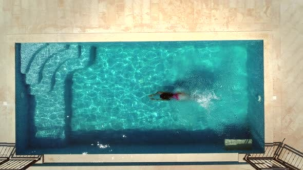 Thumbnail for Aerial view of young woman diving into swimming pool.