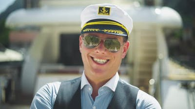 Smiling captain standing in marina