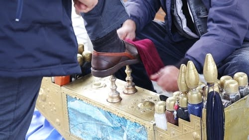 Senior Shoeshine Man Sitting On His Workplace And