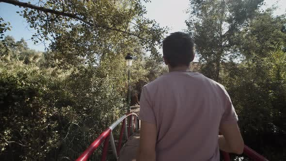 Thumbnail for YOUNG CONFIDENT MEN WALKING THROUGH JUNGLE FOREST OVER BRIDGE IN MOROCCO ON SUNNY DAY