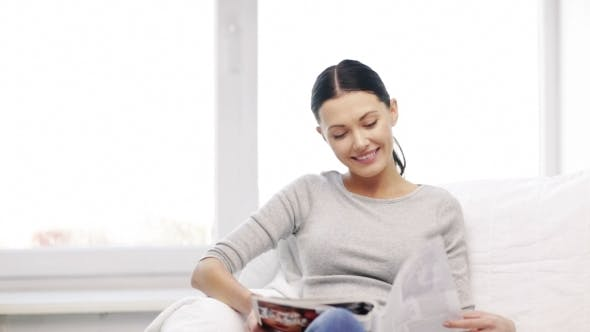 Thumbnail for Smiling Woman Reading Magazine At Home