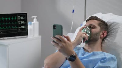 Man in Hospital with the Mobile Phone and Earphones Lying Alone in Bed