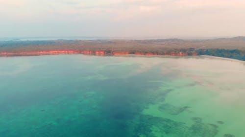Aerial: uncontaminated coastline beach sunset Kei Islands Maluku Indonesia