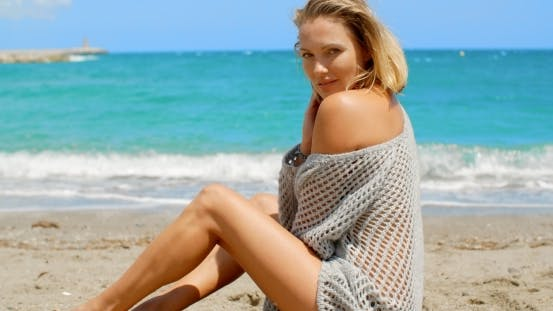 Cover Image for Woman Wearing Grey Sweater Sitting On Sandy Beach