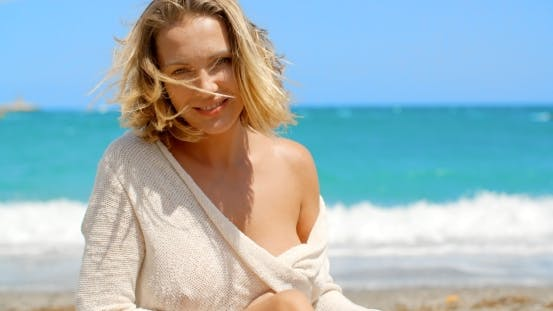 Cover Image for Blond Woman With Wind Swept Hair Sitting On Beach