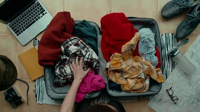 Woman Unpacks Suitcase After Travel Make Mess