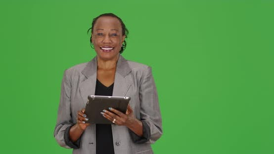 Thumbnail for A black businesswoman laughs while using her tablet on green screen