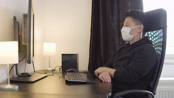Thumbnail for A Young Asian Man in a Face Mask Looks at the Desktop Computer Screen at Home Then Looks at Camera