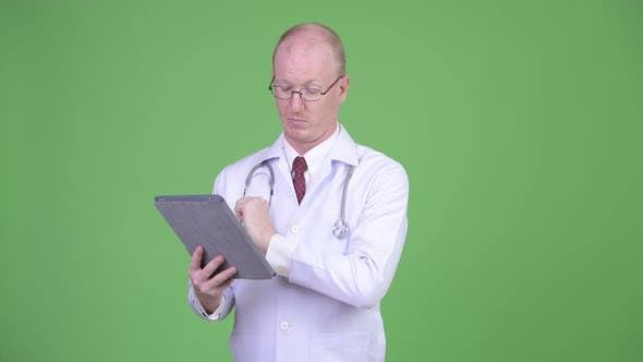 Thumbnail for Mature Bald Man Doctor Using Digital Tablet