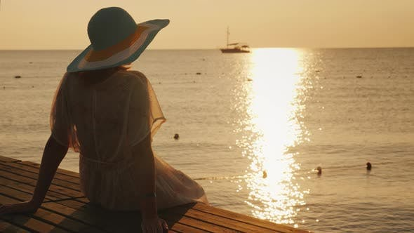 Thumbnail for A Romantic Woman in a Hat Sits on the Pier in the Early Morning. A Ship Is Visible in the Distance