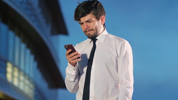 Thumbnail for Concentraited businessman texting message on smartphone.
