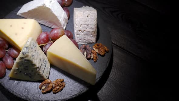 Cover Image for Assorted Cheeses with Nuts and Fruits on the Table, Rotating Video