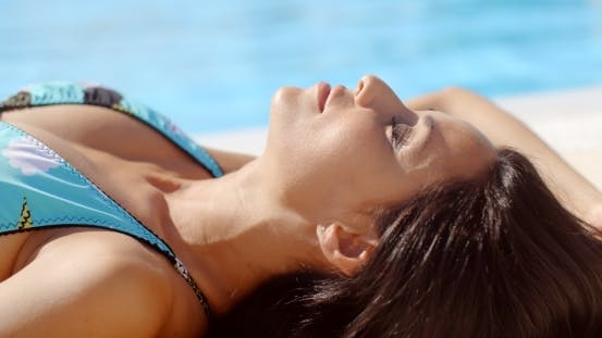 Thumbnail for Gorgeous Young Lady Sunbathing At The Poolside