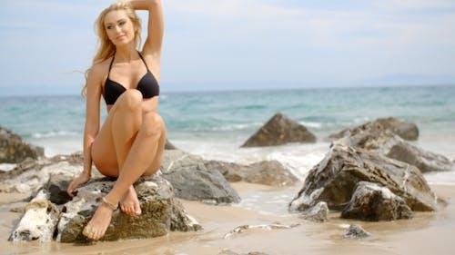 Blond Woman In Bikini Sitting On Boulder On Beach