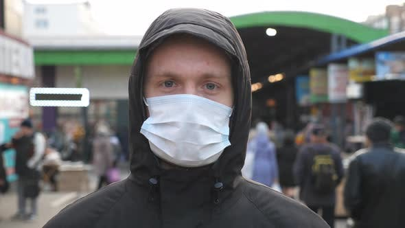 Thumbnail for Portrait of Young Man with Medical Face Mask Stands at City Street. Guy Wearing Protective Mask From