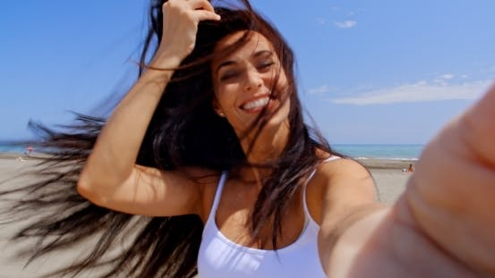 Thumbnail for Smiling Woman Taking Self Portrait On Windy Beach