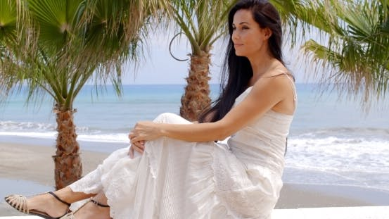 Thumbnail for Woman In White Dress Sitting On Beach Wall