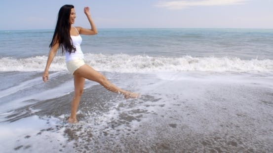 Thumbnail for Carefree Woman Kicking Up Water On Tropical Beach