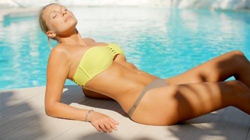 Woman Wearing Bikini Suntanning By Swimming Pool