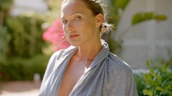 Thumbnail for Woman In Grey Robe Outdoors Looking At Camera