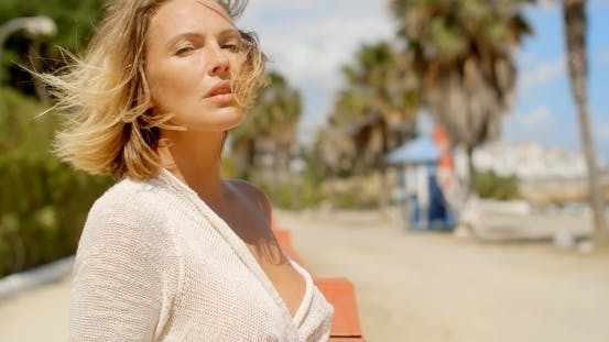 Thumbnail for Blond Woman With Wind Swept Hair Standing On Beach