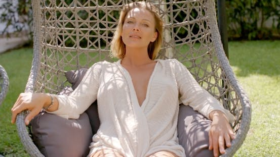 Thumbnail for Woman Relaxing In Outdoor Hanging Chair In Garden