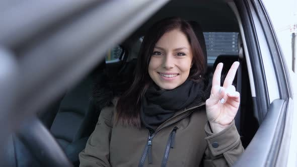 Thumbnail for Victory Sign by Young Woman Sitting in Car