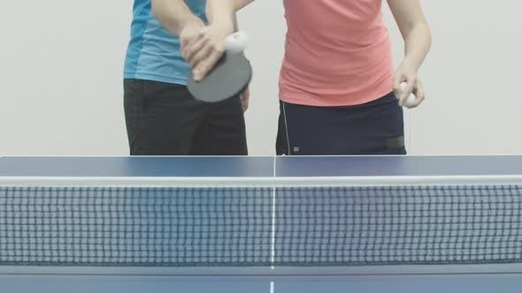 Unerkennbare Frau zeigt Ball, der dem Mann im Tischtennis dient. Weibliche kaukasische Trainer Lehre