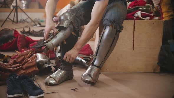 A Man Putting on an Armour on His Legs for the Knights Battle Training